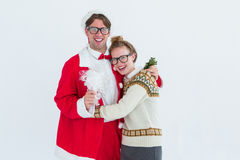 Geeky hipster in santa costume hugging his girlfriend Royalty Free Stock Images