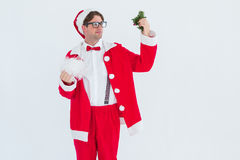 Geeky hipster in santa costume looking at mistletoe Stock Photography