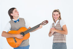 Geeky hipster serenading his girlfriend with guitar Stock Image