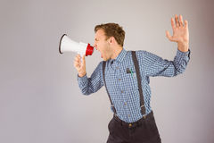 Geeky hipster shouting through megaphone Royalty Free Stock Photography