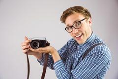 Geeky hipster som rymmer en retro kamera Royaltyfria Bilder