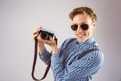 Geeky hipster som rymmer en retro kamera Arkivfoton