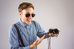 Geeky hipster som rymmer en retro kamera Royaltyfri Fotografi