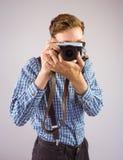 Geeky hipster som rymmer en retro kamera Fotografering för Bildbyråer