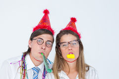 Geeky hipster wearing a party hat with blowing party horn Royalty Free Stock Photos