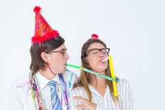 Geeky hipster wearing a party hat with blowing party horn Stock Images