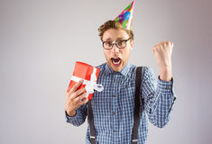Geeky hipster wearing party hat holding gift Stock Photo
