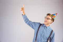 Geeky hipster wearing party hat pointing Stock Photos