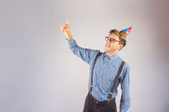 Geeky hipster wearing party hat pointing. On grey background Stock Images