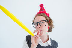 Geeky hipster wearing a party hat wig blowing party horn Royalty Free Stock Photo