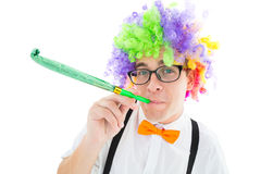 Geeky hipster wearing a rainbow wig blowing party horn Royalty Free Stock Image