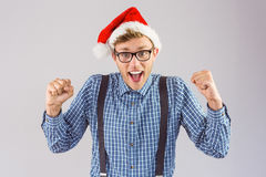 Geeky hipster wearing santa hat. On grey background Royalty Free Stock Image