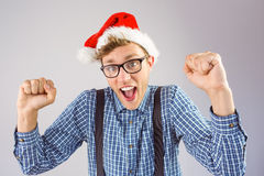 Geeky hipster wearing santa hat. On grey background Royalty Free Stock Photos
