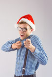 Geeky hipster wearing santa hat. On grey background Royalty Free Stock Images