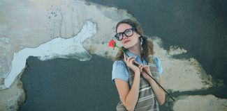 Composite image of geeky hipster woman holding rose. Geeky hipster woman holding rose  against rusty weathered wall Royalty Free Stock Photography