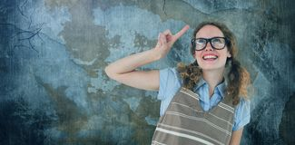 Composite image of geeky hipster woman pointing up. Geeky hipster woman pointing up  against rusty weathered wall Stock Image