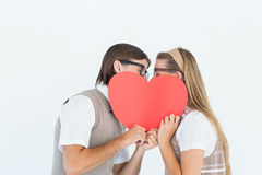 Geeky hipsters kissing behind heart card Royalty Free Stock Photography