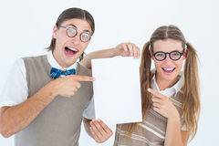 Geeky hipsters pointing at poster Royalty Free Stock Photos