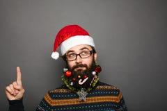 Geeky młody człowiek wskazuje up w Santa Claus kapeluszu obraz royalty free