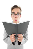 Geeky preacher reading from black bible Stock Image