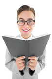 Geeky preacher reading from black bible Royalty Free Stock Photos