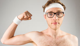 Geeky shirtless hipster flexing bicep Royalty Free Stock Photography