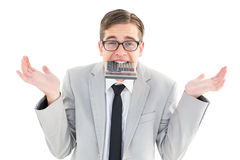Geeky shrugging businessman biting calculator Royalty Free Stock Images