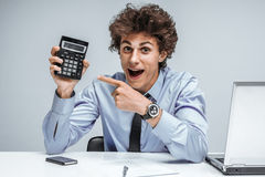 Geeky smiling businessman showing calculator Royalty Free Stock Photos