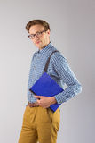 Geeky student holding a notebook. On grey background Stock Photography