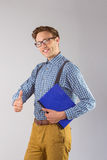 Geeky student holding a notebook. On grey background Royalty Free Stock Photography