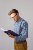 Geeky student reading a book. On grey background Stock Photo