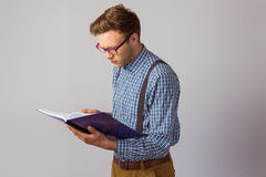 Geeky student reading a book. On grey background Stock Photography