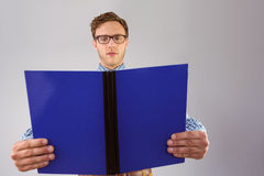Geeky student reading a book. On grey background Royalty Free Stock Photography