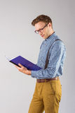 Geeky student reading a book Stock Photography