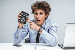 Geeky surprised businessman showing calculator Royalty Free Stock Images