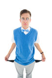 Geeky young hipster showing empty pockets. On white background Royalty Free Stock Photography