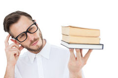 Geeky young man looking at pile of books Royalty Free Stock Photos