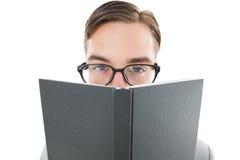Geekymens die over boek kijken Stock Foto's