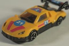 Geel autostuk speelgoed op witte achtergrond Stock Fotografie