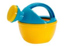 Geel-blauw gieterstuk speelgoed op wit geïsoleerde achtergrond Stock Foto's