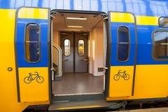 Geel-blauwe wagen van traditionatreinen in Holland Deur voor fiets stock afbeeldingen