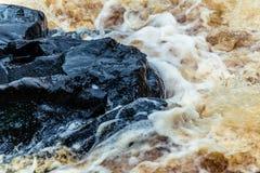 Geel-bruine plonsen van water van de waterval van Akhvenkoski in Karelië Royalty-vrije Stock Fotografie