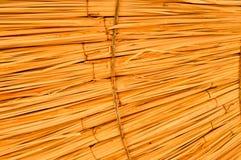 Geel droog golf geribbeld convex volumetrisch stro, hooi met lange takken en hellende hellingen De achtergrond stock foto