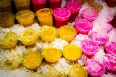 Geel en rood sap in de plastic glazen Stock Foto's