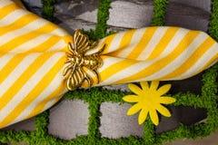 Geel en wit kernachtig linnenservet met gouden bijenservetring op een placemat die als straatstenen met de graslente t kijkt stock foto