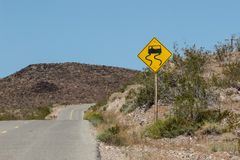 Geel en zwart glad teken langs een weg stock fotografie