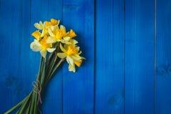 Geel gele narcissenboeket op blauwe houten achtergrond, Pasen-kaart Stock Foto