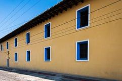Geel geschilderd huis in de stad met blauwe vensters Stock Foto's