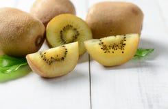 Geel gesneden kiwifruit op witte houten achtergrond Royalty-vrije Stock Foto's