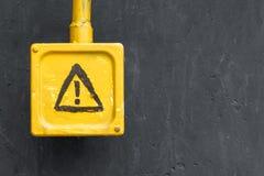 Geel gevaarsteken op de grijze muur Stock Foto